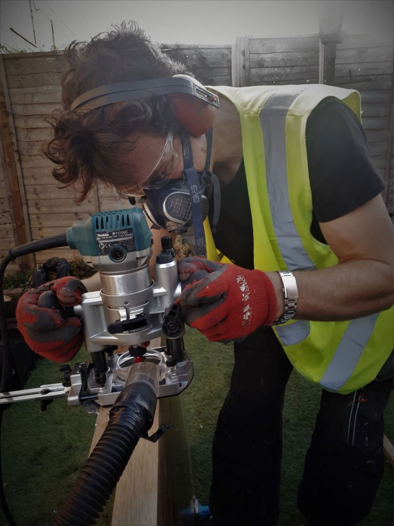 This picture is of Alex Hykel, from Hykel Carpentry putting hinges in a door. He is using a router to cut the space in the door that the hinge sits in. He is using the correct Personal Protection Equipment (PPE). These are ear defenders, safety specs,, a respiratory mask and gloves.